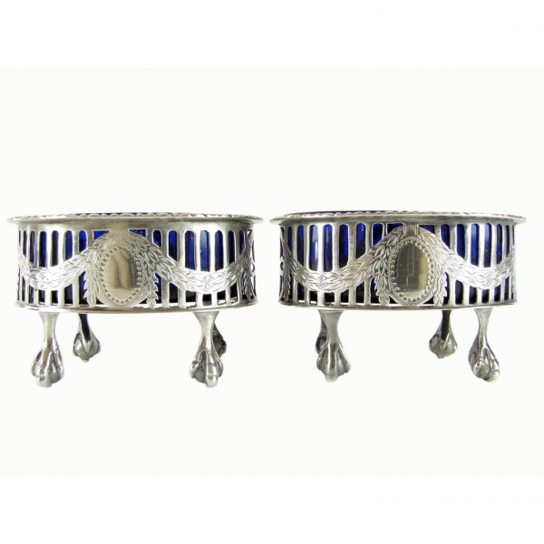 A pair of antique solid silver salts with blue glass liners