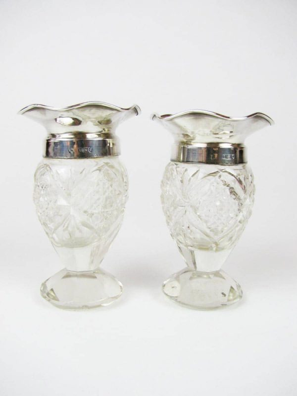 A pair of small cut glass and solid silver vases hallmarked London 1931-32